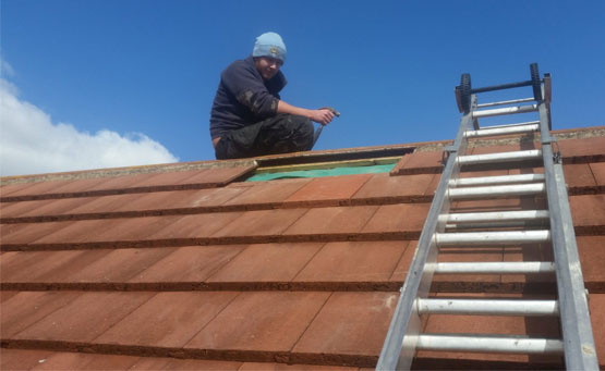 Roofer Repairing Red Tile Roof.
